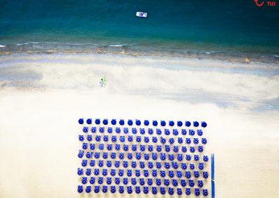 Strand mit Sonnenschirmen von oben